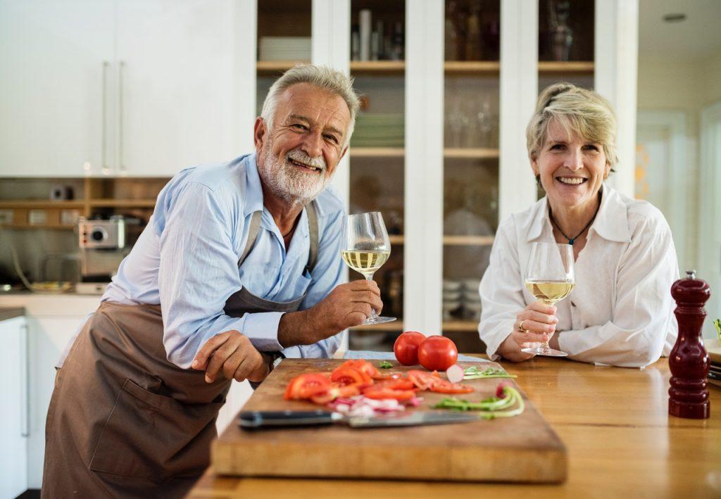 Et eldre par på kjøkkenet med et glass vin hver.